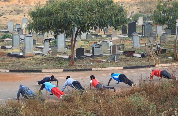 Sem locais para treinar, moradores de Harare têm usado cemitério para praticar exercícios (Foto: Tsvangirayi Mukwazhi/AP)