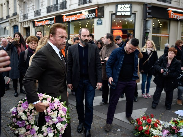 O ator e ex-governador da Califórnia, Arnold Schwarzenegger, carrega coroa de flores para homenagem às vítimas do ataque de terroristas à casa de shows Bataclan, em Paris, no sábado (5) (Foto: AFP Photo/Martin Bureau)
