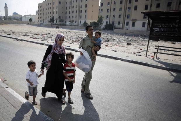 Palestinos fogem de bombardeio israelense em Bet Lahiya, no norte da Faixa de Gaza, nesta segunda-feira (21) (Foto: Finbarr O'Reilly/Reuters)