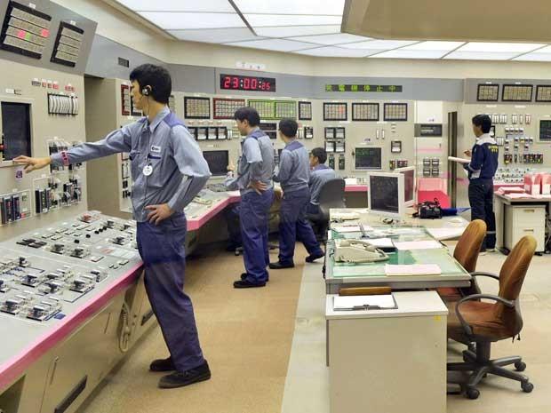 Funcionários monitoram a usina de Fukushima a partir de um centro de controle. (Foto: Kyodo News / Via AP Photo)