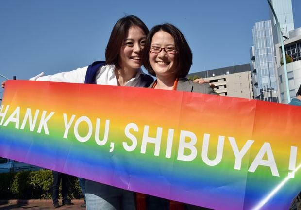 O casal Hiroko Masuhara e Koyuki Higashi exibe faixa agradecendo ao distrito de Shibuya, em Tóquio, por ser o primeiro a reconhecer a união de casais homossexuais no país nesta terça-feira (31) (Foto: Yoshikazu Tsuno/AFP)