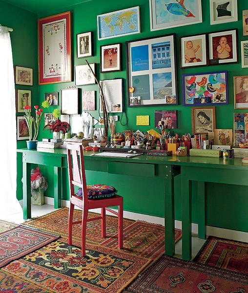 O escritório do diretor de arte e de cinema Thiago Bastos tem paredes verde-esmeralda com muitos quadros. No chão, uma composição de tapetes pequenos aquece o ambiente  (Foto: Victor Affaro/Casa e Jardim)