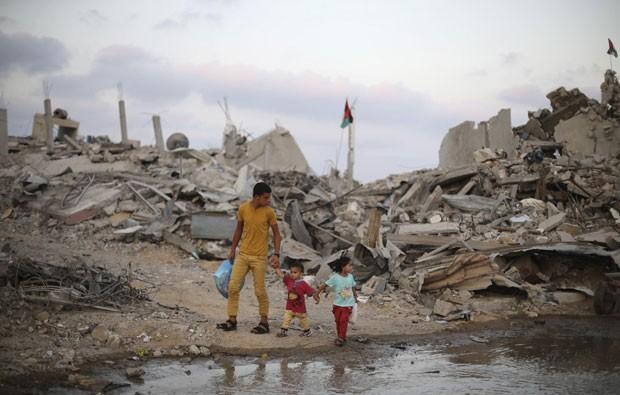 Palestinos caminham em meio a ruínas de casas em Khan Younis, no sul da Faixa de Gaza, nesta segunda-feira (18) (Foto: Ibraheem Abu Mustafa/Reuters)