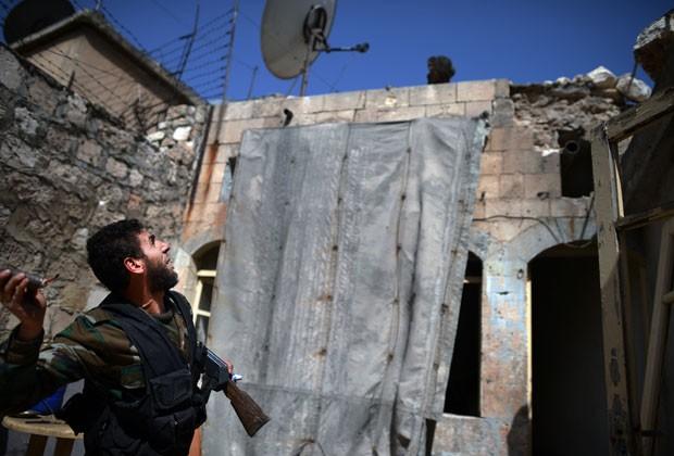 Rebelde sírio se prepara para jogar granada contra forças do regime em Aleppo (Foto: AFP)