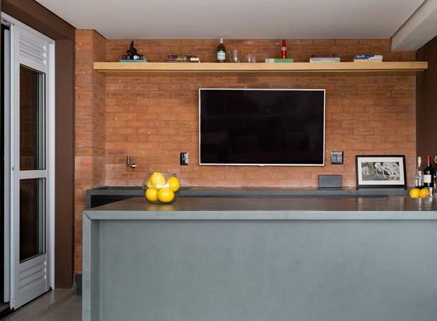 A varanda gourmet também ganhou revestimento de tijolinhos Pasinato. Marcenaria desenhada pelo escritório Drops e executada pela REM Marcenaria (Foto: Julia Ribeiro/Divulgação)