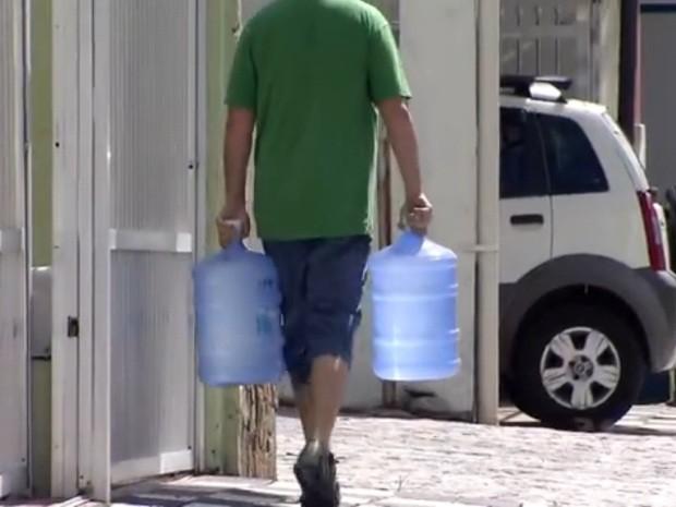 Moradores são obrigados a comprar água em galões em Guarujá (Foto: Reprodução / TV Tribuna)