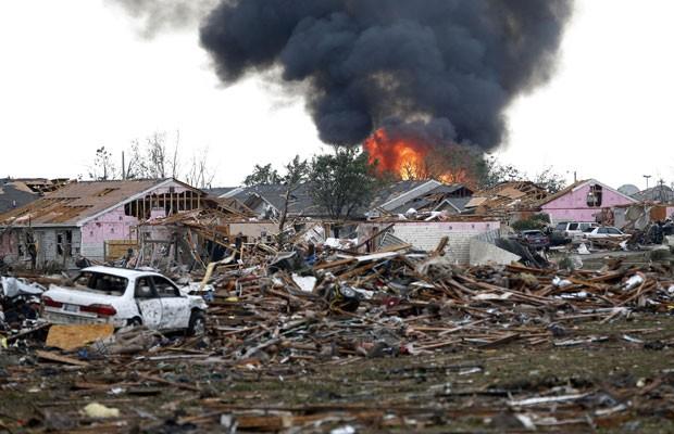 Pneu pega fogo em Moore, Oklahoma, após um tornado nesta segunda-feira (20) (Foto: Sue Ogrocki/AP)