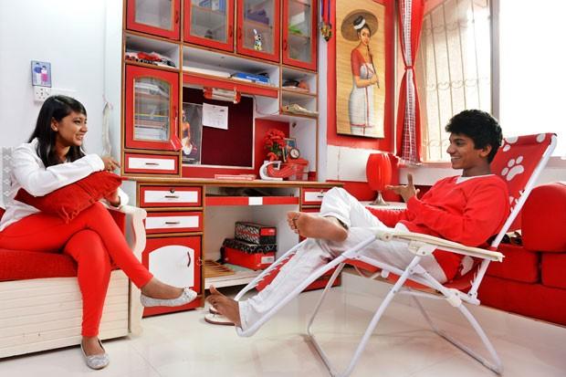 Para não desagradá-lo, mulher e filhos também usam vermelho e branco (Foto: Manjunath Kiran/AFP)