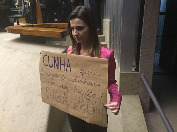 A deputada Clarissa Garotinho (PR-RJ) segura cartaz com dizeres sobre Eduardo Cunha atrás da mesa da Câmara (Foto: Nathalia Passarinho / G1)