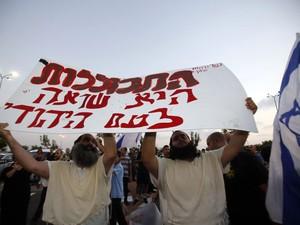 Membros da organização radical Lehava carregam cartaz que diz 'Assimilação é o genocídio do povo judeu' em protesto contra o casamento de Mahmoud Mansour e Morel Malcha, na cidade israelense de Rishon Letzion (Foto: AFP Photo/Gali Tibbon)