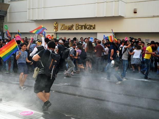 Pessoas tiveram que correr depois que a polícia usou gás lacrimogêneo e canhões de água durante a Parada Gay em Istambul, neste domingo (28) (Foto: Ozan Kose/AFP)