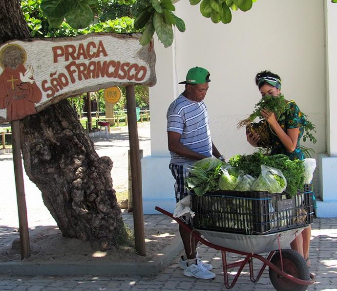 Bela Gil dá cheirinho nos temperos verdes do vendedor (Foto: Nathália Gomes/Gshow)