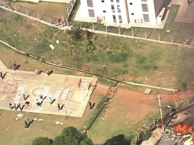 Moradores escrevem mensagens na quadra de esportes de condomínio em Itaquera, Zona Leste (Foto: Reprodução / Globo News)