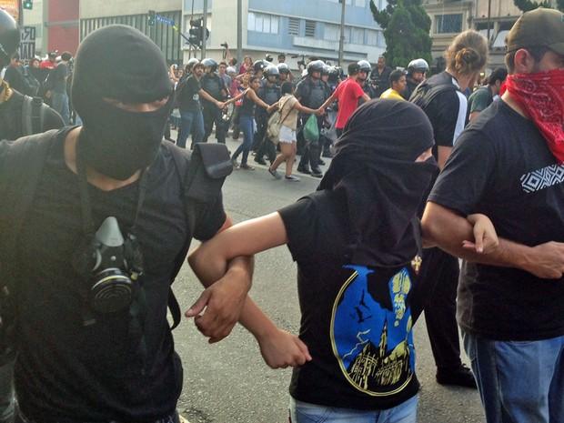 Grupo esconde o rosto na descida da Rua da Consolação (Foto: Marcelo Mora/G1)