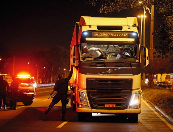 Policial aborda caminhoneiro na Avenida Brasil no Rio (Foto:  Domingos Peixoto / Agência o Globo)
