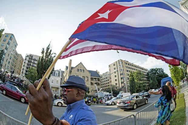 Homem agita a bandeira cubana em frente à nova embaixada do país em Washington, nos EUA, nesta segunda-feira (20) (Foto: Paul J. Richards/AFP)