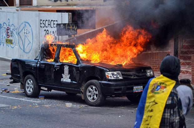 Manifestantes anti-governo incendiaram veículo da Guarda Nacional da Venezuela nesta terça-feira (29) em Caracas (Foto: Carlos Becerra/AFP)