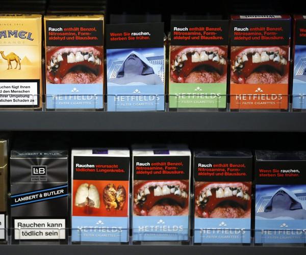 Maços de cigarro com capas contendo ilustrações que simulam bocas e dentes danificados pelo uso de cigarro. A União Europeia está discutindo novas regras para venda de derivados de tabaco. A previsão é que, até 2015, todos os maços tenham 75% do seu espaç (Foto: Fabrizio Bensch/Reuters)