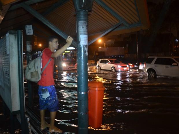 Rapaz espera ônibus no banco do ponto por causa de chuva no Varadouro (Foto: Walter Paparazzo/G1)