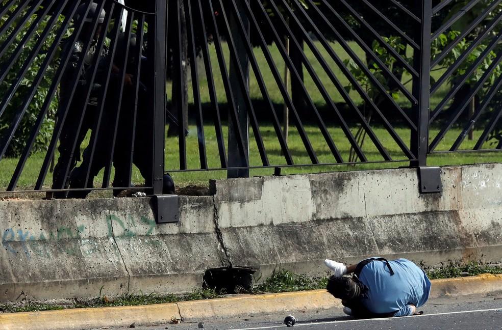 Manifestante cai após ser atingido por tiro disparado por forças de segurança durante protesto em Caracas, na quinta-feira (22) (Foto: Carlos Garcia Rawlins/ Reuters)