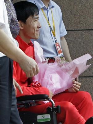 Após cirurgia em Londres, Liu Xiang desembarca no aeroporto de Xangai em cadeira de rodas (Foto: Reuters)