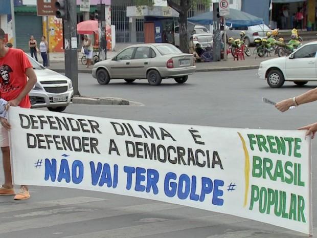 Manifestantes seguram faixas nos semáforos em Cuiabá (Foto: Reprodução/ TVCA)