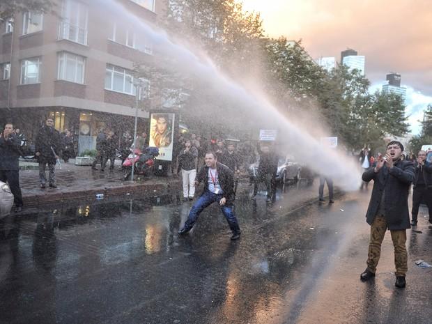 A polícia turca usa um canhão de água para dispersar apoiadores e funcionários dos canais Bugün TV e Kanaltürk em Istambul, na Turquia, durante um protesto. A polícia assumiu o conrole dos canais, que pertencem a um grupo de comunicação ligado à oposição (Foto: Usame Ari/Zaman/AFP)