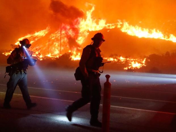 Bombeiros do condado de Ventura, na Califórnia, combatem incêndio na manhã de sábado (26) (Foto: Reuters/Gene Blevins )