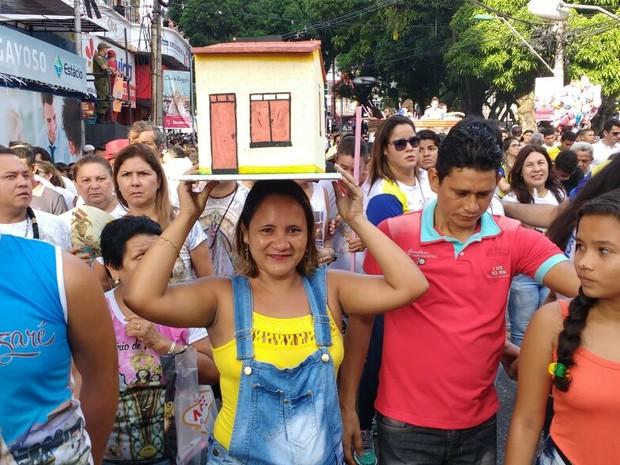 Promesseira leva casa na cabeça no Círio 2016 (Foto: Alexandre Yuri / G1)