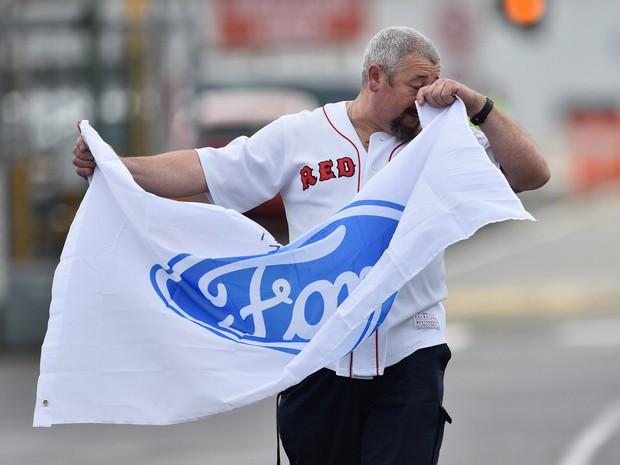Trabalhador carrega bandeira da Ford ao deixar fábrica da empresa, em Melbourne, na Austrália, nesta sexta (7) (Foto: AAP/Julian Smith/via REUTERS )