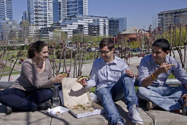 Lucia, Fernando e Enrique compartilham uma pizza como almoço em um dos parques de Puerto Madero. Eles trabalham em um prédio moderno, ao fundo (Foto: Haroldo Castro/Época)