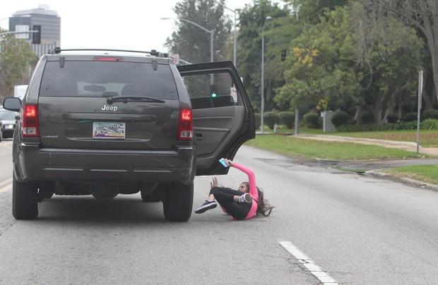 Fã de Justin Bieber cai no asfalto ao pular do carro de sua mãe (Foto: Grosby Group)