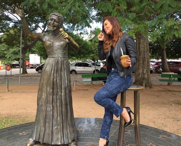 Com o chimarrão na mão, Carol Nakamura 'canta' com a estátua de Elis Regina (Foto: Arquivo Pessoal)