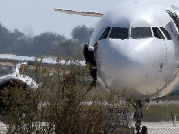 Um homem saiu pela janela do cockpit do Airbus A320 da Egyptair Airbus, no aeroporto de Larnaca, no Chipre, na manhã desta terça-feira (29) (Foto: Yiannis Kourtoglou/ Reuters)