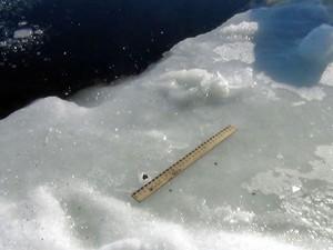 Imagem divulgada pelo Departamento de Polícia da região de Cheliabinsk neste sábado (16), mas feita na sexta (15), mostra pequeno fragmento encontrado na beira do lago Chebakul, local onde, supostamente, o meteoro teria caído (Foto: Divulgação/Departamento de Polícia de Cheliabinsk)