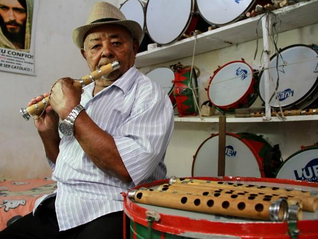 Mestre Bia toca pífano na sala onde guarda instrumentos e ensaia com a banda (Foto: Waldson Costa / G1)