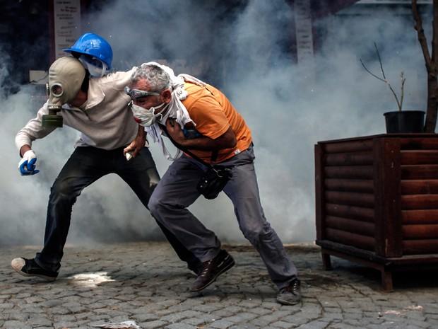 11 de junho - Manifestantes fogem de bomba de gás lacrimogênio lançada pela polícia na Praça Taksim. (Foto: Angelos Tzortzinis/AFP)