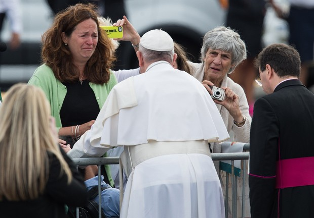 Mulher chora ao ver papa Francisco se aproximar e abençoar seu filho com deficiência física em sua chegada à Filadélfia  (Foto: Nicholas Kamm/AFP)