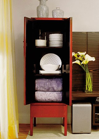 Com 0,50 x 1,80 x 0,50 m, o armário tem o interior pintado de preto e três prateleiras. Nas duas de cima ficam as louças. Embaixo, mantas da MMartan. No alto, vasos da L'Oeil (Foto: Casa e Jardim)