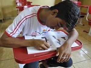 Aluno conta que aprendeu a escrever o próprio nome após entrar na escola, em Itumbiara, Goiás (Foto: Adriano Zago/G1)
