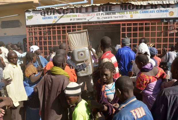 Moradores saqueiam lojas em Timbuktu, no Mali, nesta terça-feira (29) (Foto: AFP)