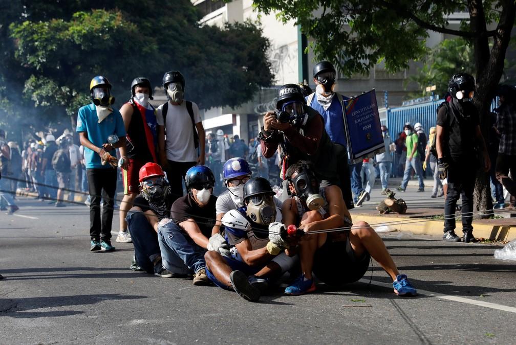 Opositores usam estilingue para jogar bomba de fezes contra forças de segurança nesta quinta-feira (18) em Caracas (Foto: REUTERS/Carlos Garcia Rawlins )