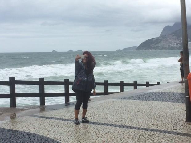 Pedestre tira selfie em dia de ressaca na orla do Rio (Foto: Matheus Rodrigues/G1)