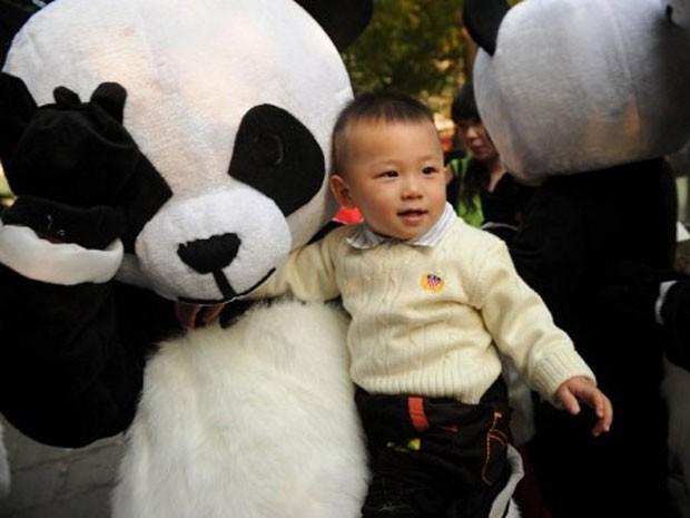 """Criança chinesa é carregada por """"urso panda"""", em Xangai, na China (Foto: Peter Parks/AFP)"""