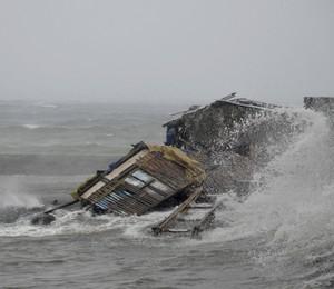 Casa ficou destruída após passagem do tufão Haiyan pela cidade de Legazpi, nas Filipinas, nesta sexta-feira (8). Cerca de 125 mil pessoas foram evacuadas de cidades que estão na rota do supertufão (Foto: AP Photo/Nelson Salting)