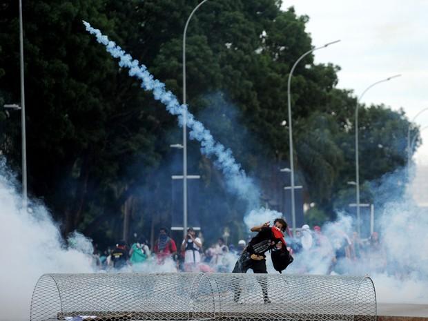 Um manifestante atira uma bomba de gás de volta para a polícia durante protesto contra a PEC 55, que limita os gastos públicos para os próximos 20 anos, na Esplanada dos Ministérios, em Brasília (Foto: Andressa Anholete/AFP)