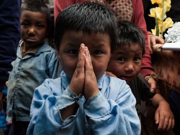 Menino nepalês faz saudação 'namastê', reverência típica (Foto: Rafael Saes/Divulgação)