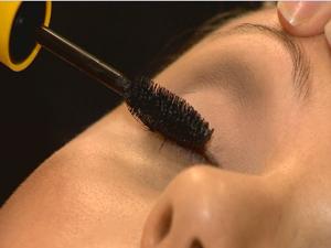 A maquiadora aplica máscara de cílios (Foto: Reprodução/RBS TV)