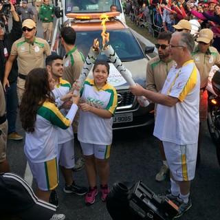 Chama olímpica é passada de um condutor para outro em Praia Grande (Foto: Solange Freitas)
