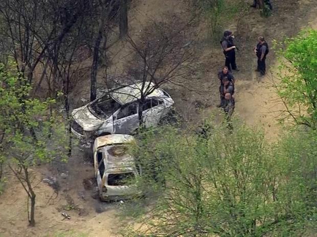 Policiais isolam área onde foram achados carros com corpos carbonizados no Chapadão (Foto: Reprodução/TV Globo)